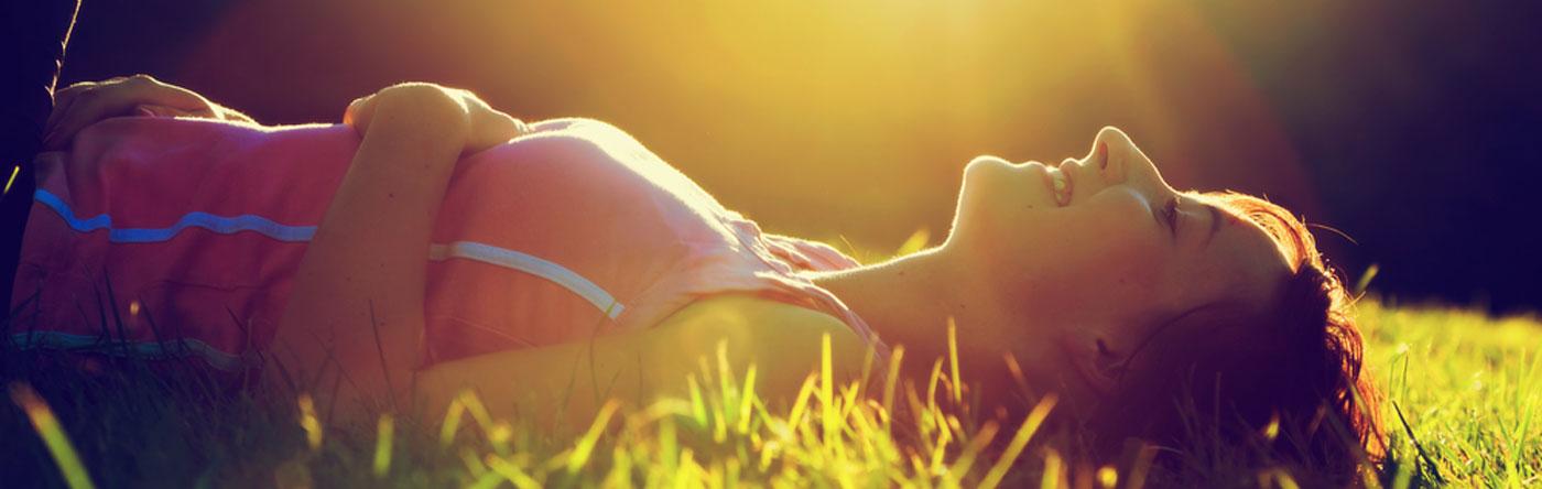 Onnellnen nainen lepää nurmikolla aamuauringon paistaessa